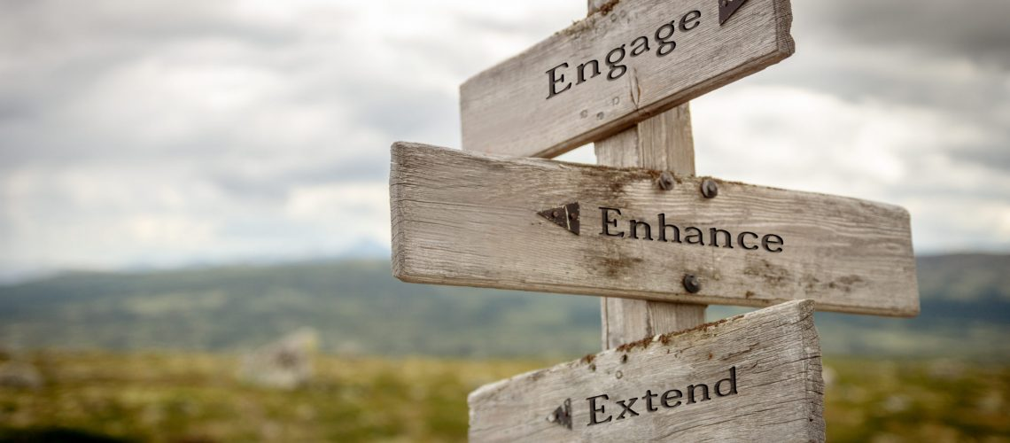 engage enhance extend text engraved on wooden signpost outdoors in nature.